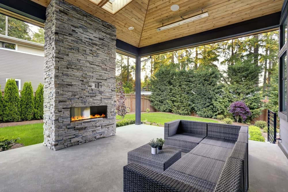 Covered patio with stone brick fireplace and concrete patio surface.