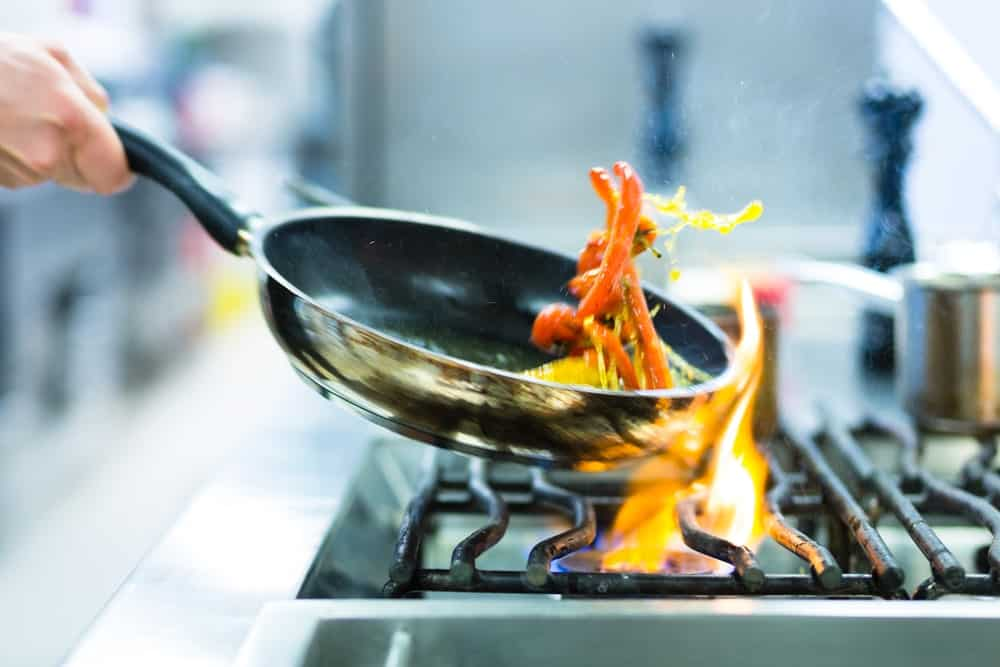 Cooking with a frying pan on a stove.