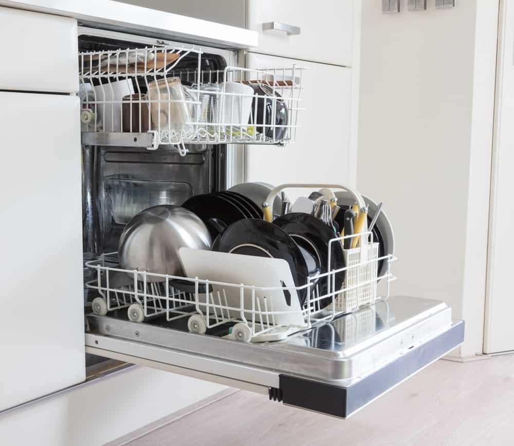 An open dishwasher full of silverware.