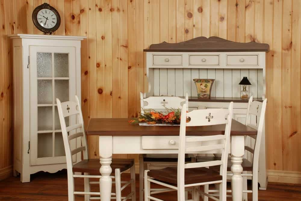Kitchen with vintage white-painted wooden furniture and a matching dining table.