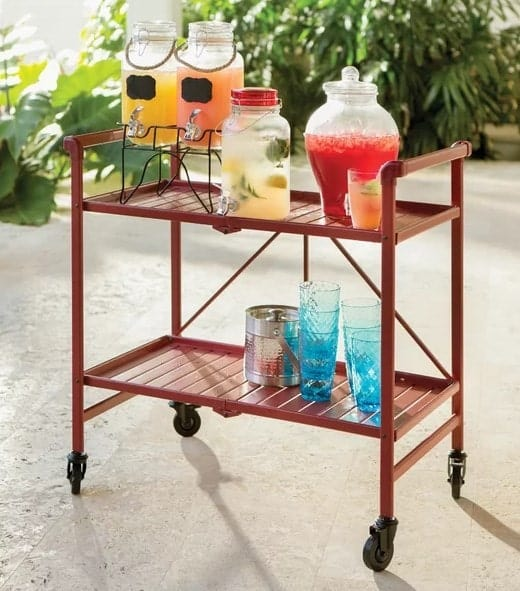 Two-tiered drink cart with different types of refreshments on top and an ice box and glasses on the lower tier.