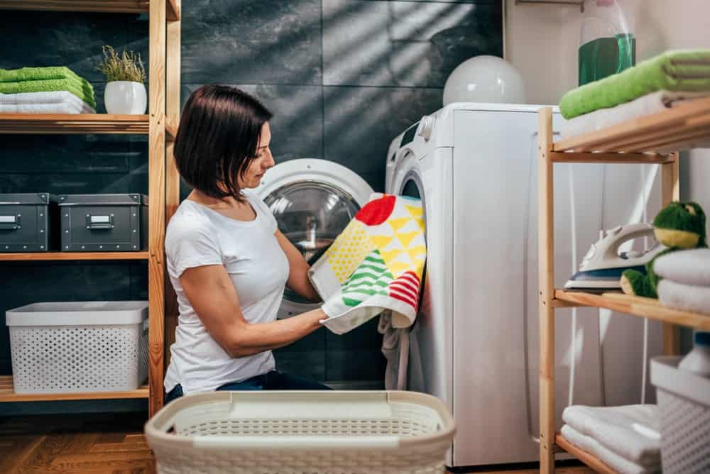 A woman takes out dry laundry from the dryer.