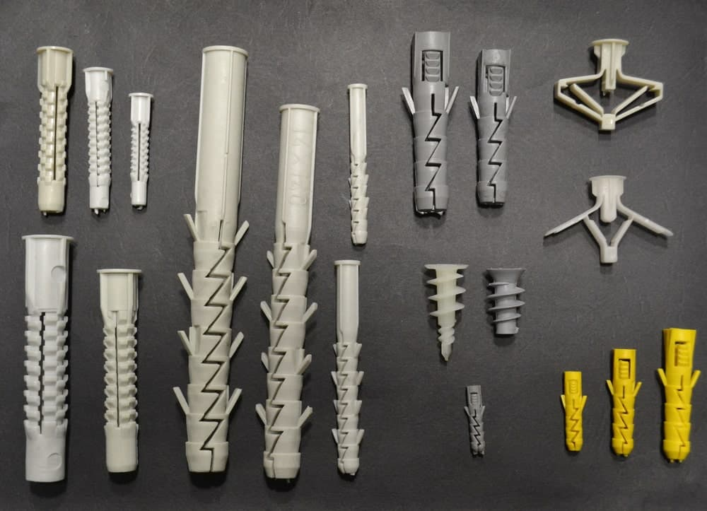 Different types of drywall anchors on a gray background.