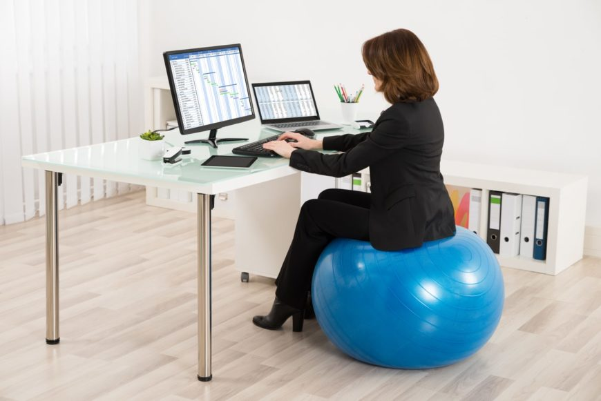 A woman sits on a fitness ball while working in her office.