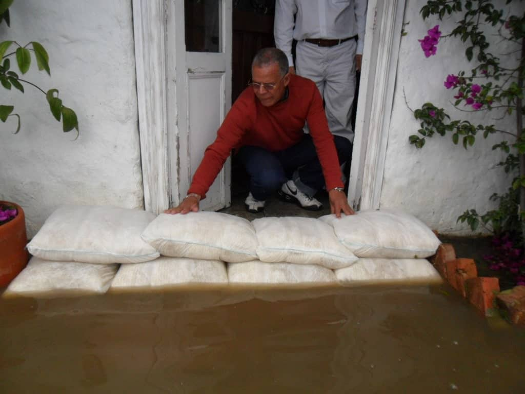 A man stacks FloodSax on the ground in front of his front door keeping the muddy floodwater from entering his house.