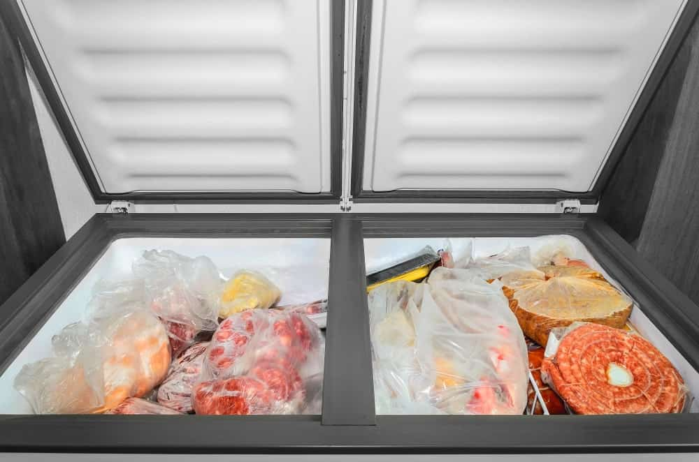 An open freezer full of frozen meat.