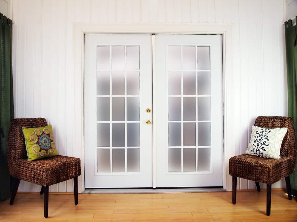 French doors flanked by rattan chairs with throw pillows.