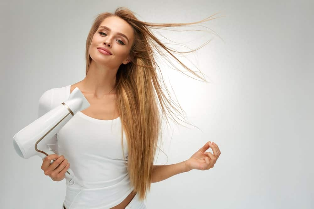 A beautiful woman using a hairdryer to dry out her straight long blonde hair.