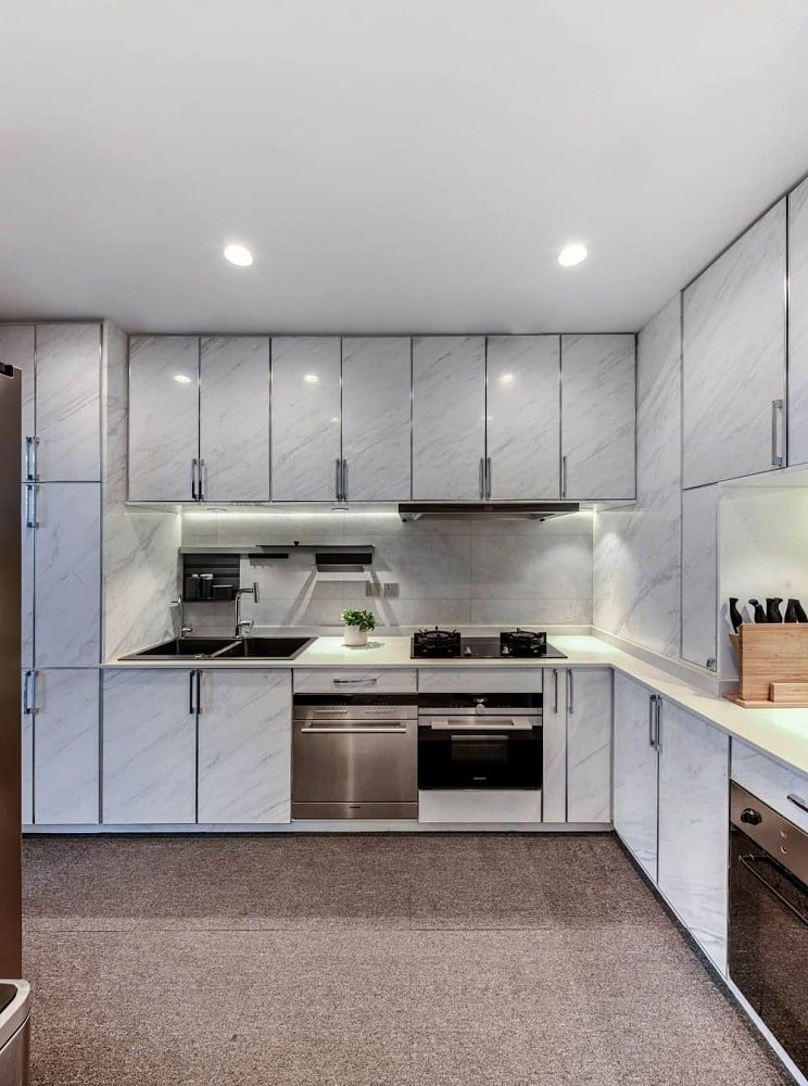 This is a white kitchen with white marble cabinet doors complemented by the stainless steel appliances and lighting.