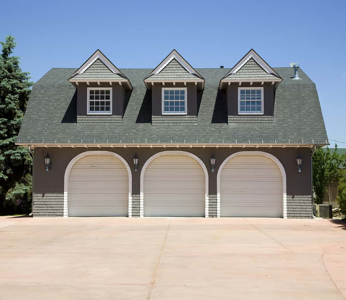 Detached 3 car garage with arched garage doors and one dormer above each garage door. This is a beautiful garage structure.