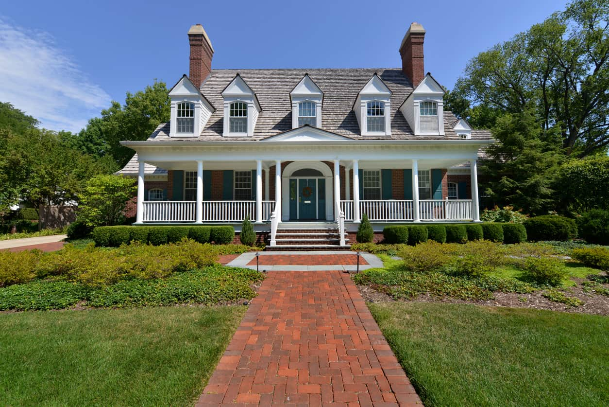 Here's an example of 5 dormers spanning the entire width of a home with a full-width porch. Brick chimneys rise up on each side above the dormers.