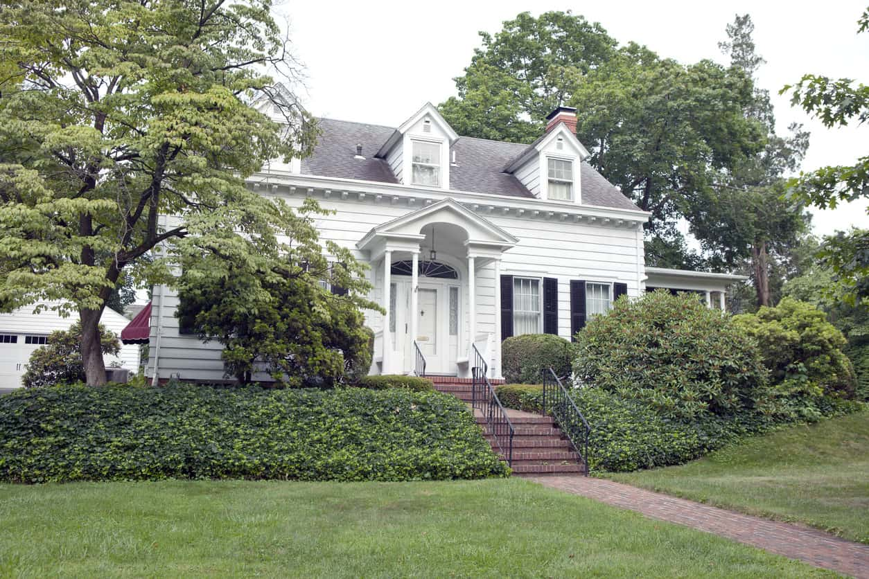 Quaint colonial style two-story home with three white dormer window making up the windows on the second floor.