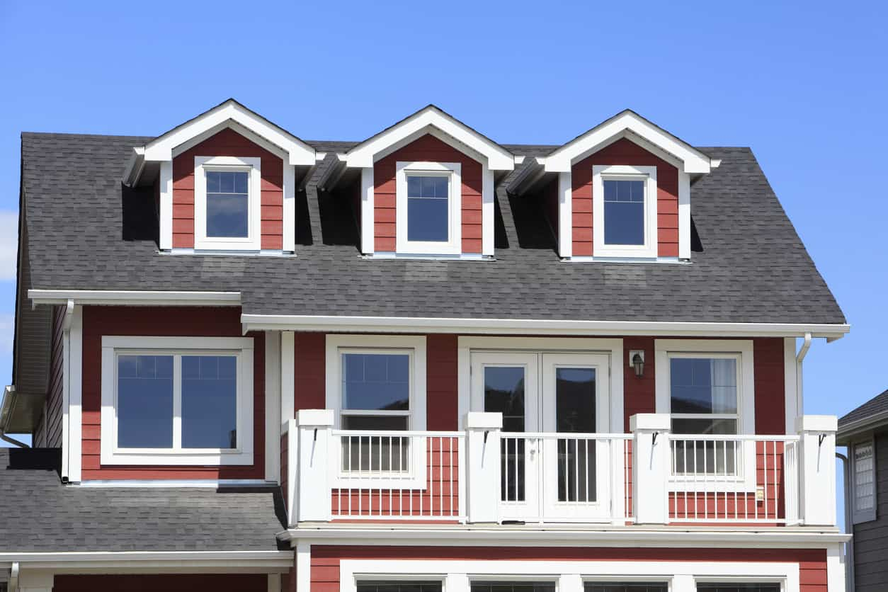 New red and white vacation home with matching red dormers with white trim.