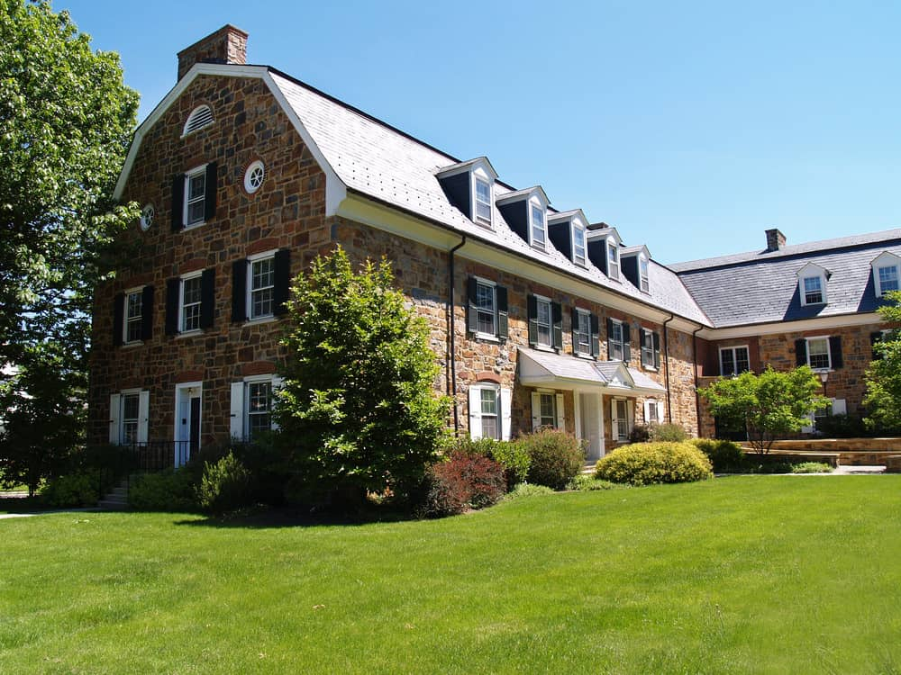 Large L-shaped brick colonial house with 7 dormer windows built into the gambrel roof.