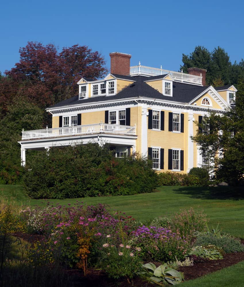 Yellow colonial house with dormer windows on all sides of the hipped roof.