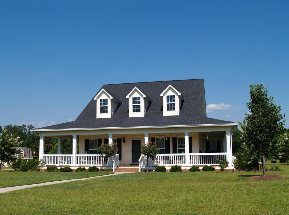 White farmhouse with wrap-around porch and dark gray roof with three white dormer windows prominently jutting out from the long sloping roof.