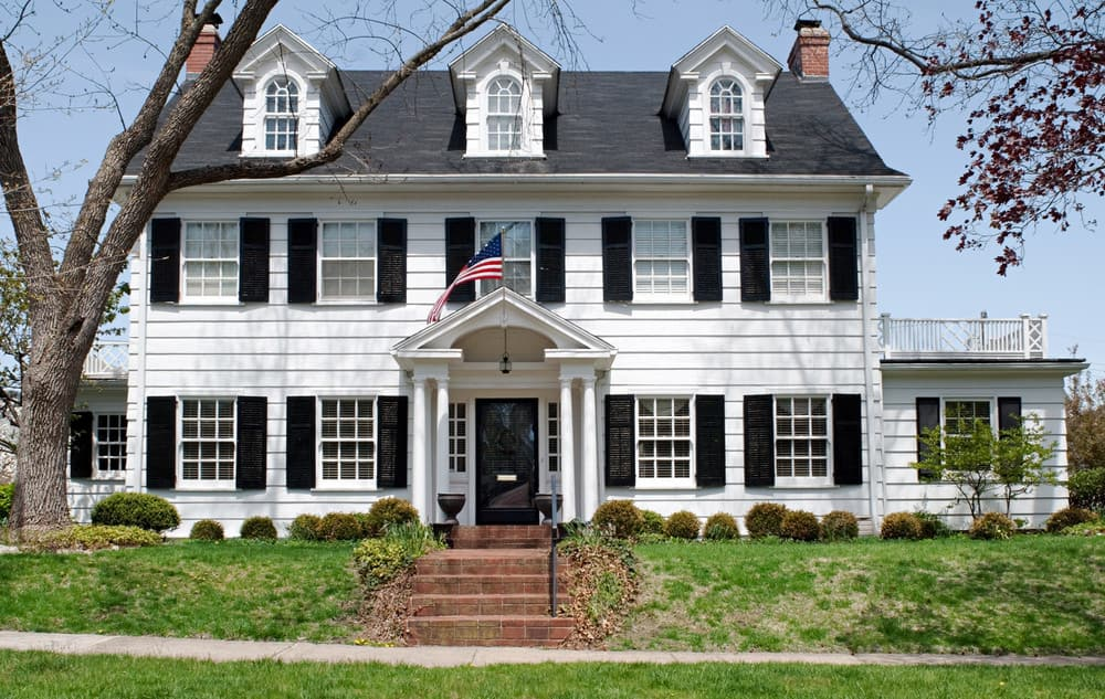 Classic white colonial home with black shutters with three handsome dormer windows in the gabled roof on the third story.