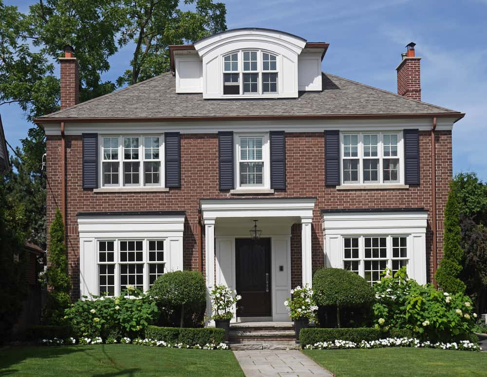 Example of a dormer window with an arched roof on the third floor of this stately brick home.