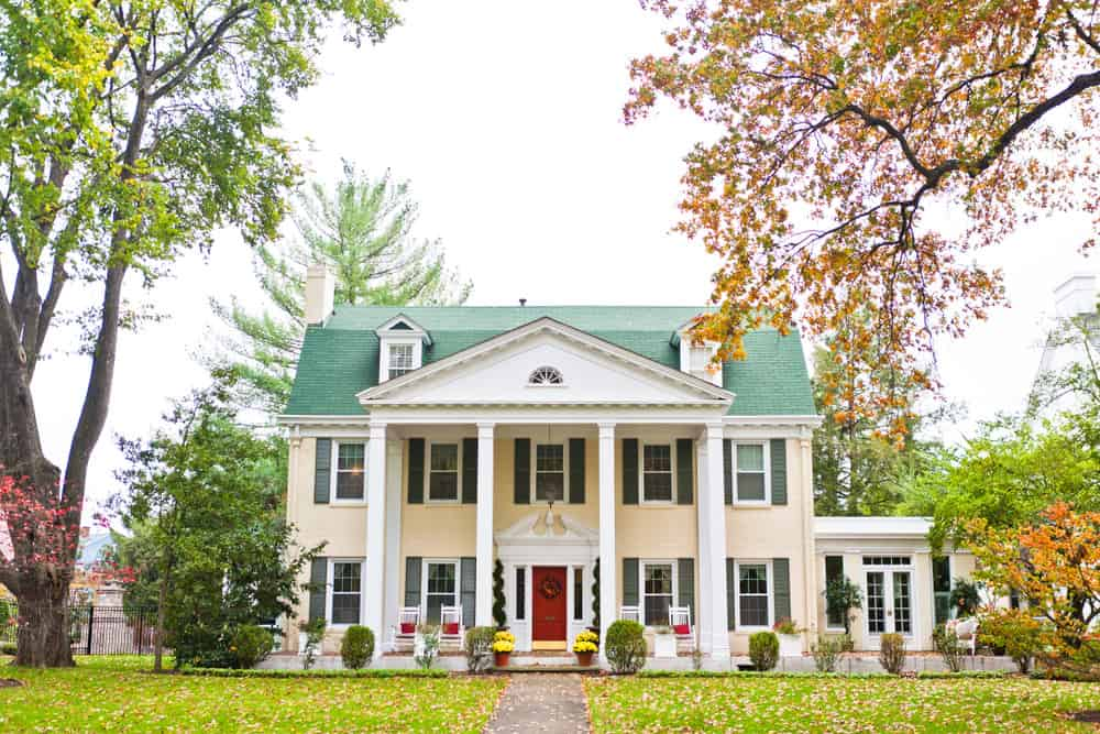 This photo of a large three story house with two story columns in front includes two tiny dormer windows jutting out of the green gambrel style roof.