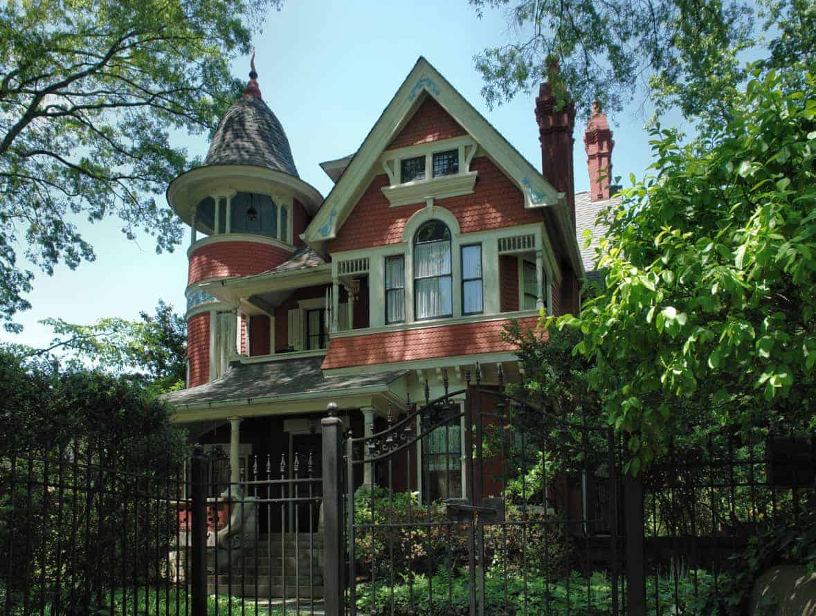 Here's a red and white Victorian style house with a turret balcony on one side of the house. Notice how the upper part of the turret is open to the outdoors, kind of like a gazebo instead of enclosed as part of the home's interior.