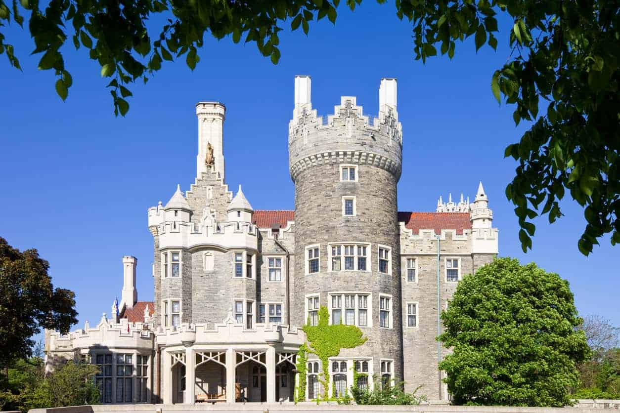 Side view of Casa Loma with a massive center round turret feature towering above the main structure.