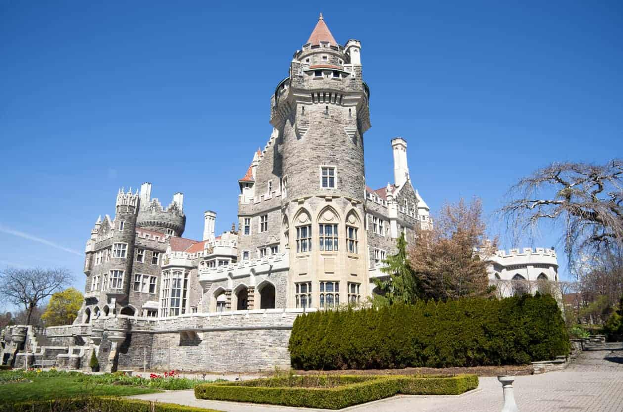 Rear view of Casa Loma including a massive tower with turret rising up in one corner. You can see multiple smaller turrets all over this structure.