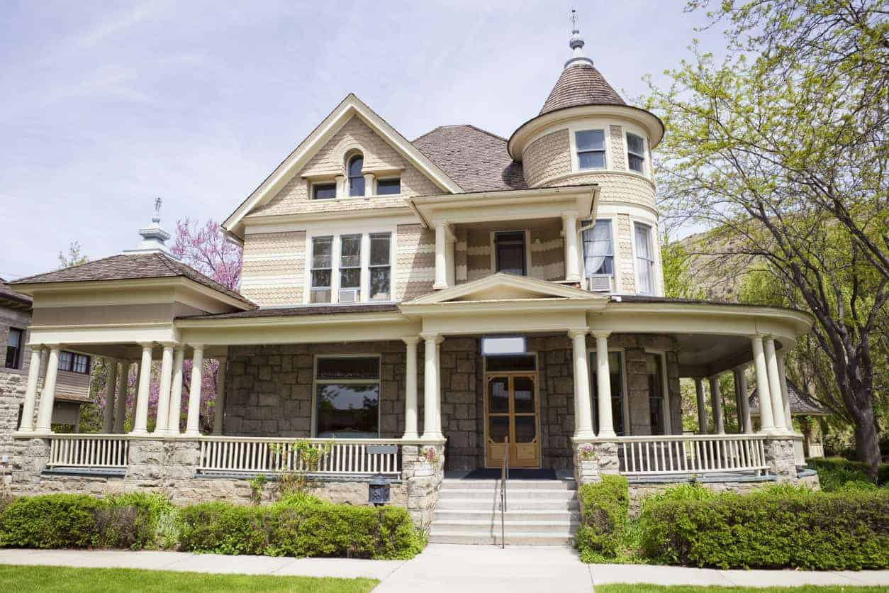 Victorian style home with a round turret on corner above large porch with shingle siding.