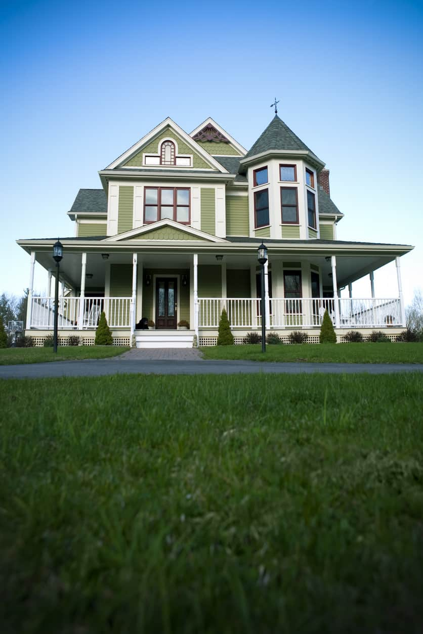 Green Victorian farmhouse with turreted bay window on corner of the home.