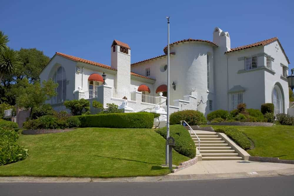 White Spanish style mansion with large windowless turret built into the main structure of the house (as opposed to being built on the side or corner where most turrets are built).