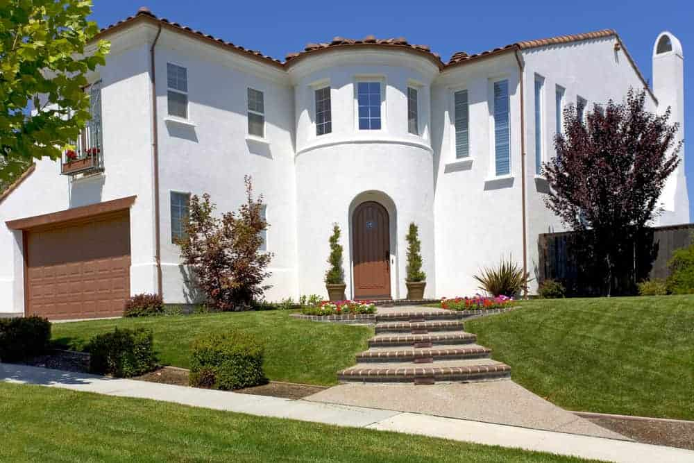 Here's a white stucco red tile roof Spanish style home built in L-shape with turret built into the center like a hinge.