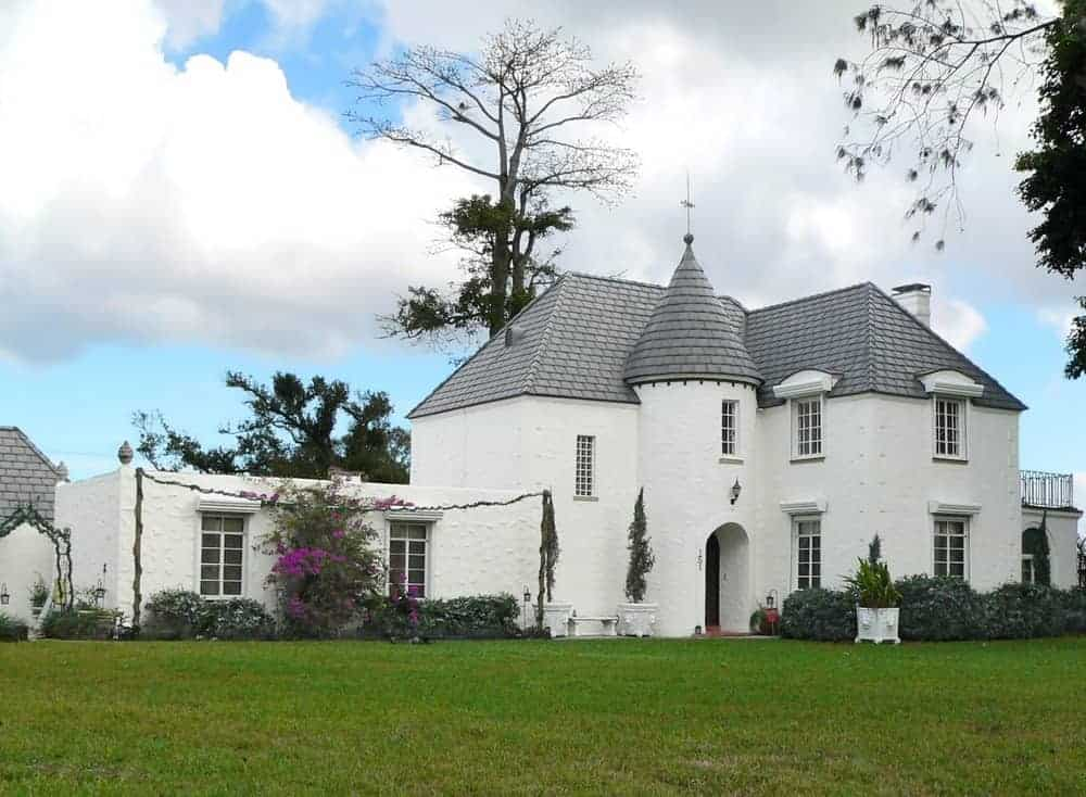 White suburban house built like a castle structure with a turret built in the center where the front door is located.
