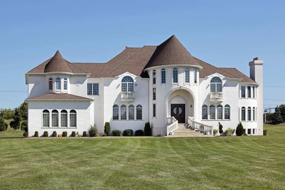 White McMansion with huge center turret structure that's the front door and foyer.