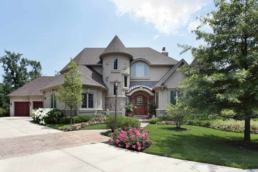 Here's a classic example of a McMansion with a turret built into the main structure of the home adjacent to the front door. It rises up as high as the rest of the house but is distinguishable because of it's separate cone roof.