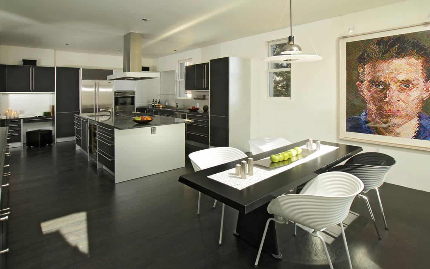 Large u-shaped black kitchen with very dark wood flooring and a black kitchen dining table.
