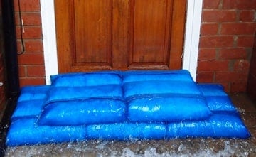 Hydrosacks placed before a residential front door keeping the floodwater at bay.