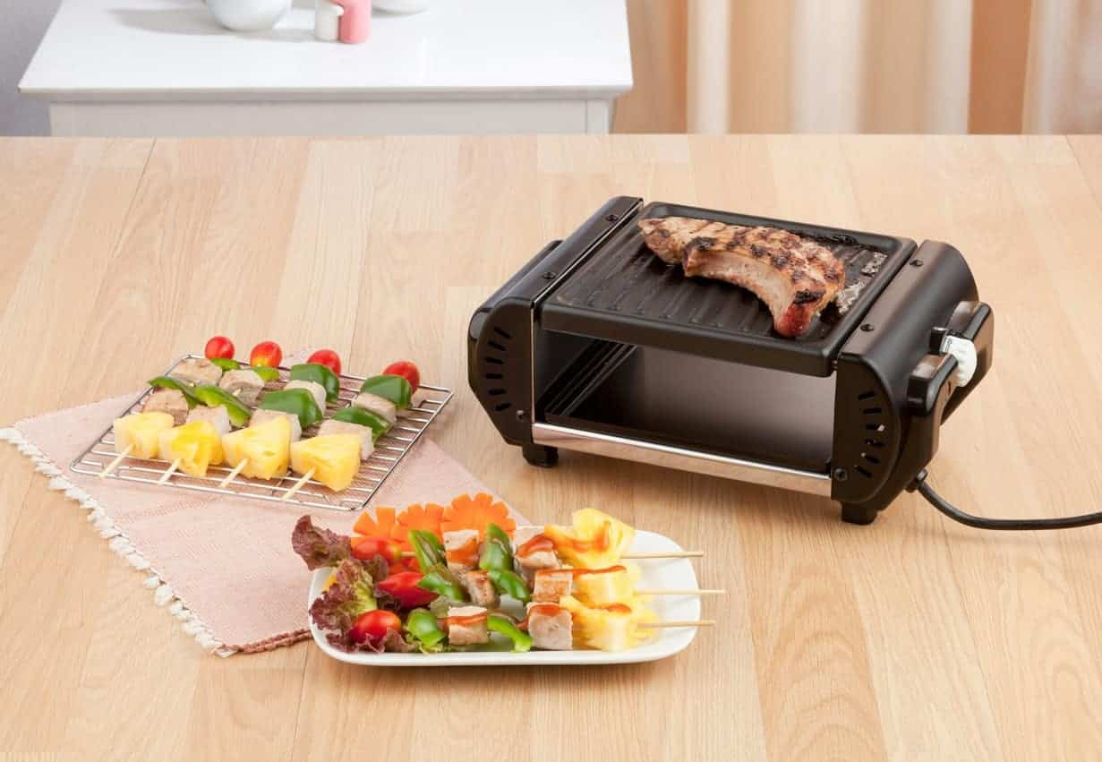 Grilling a piece of steak on the indoor electric grill beside pieces steak kebab on wooden table.