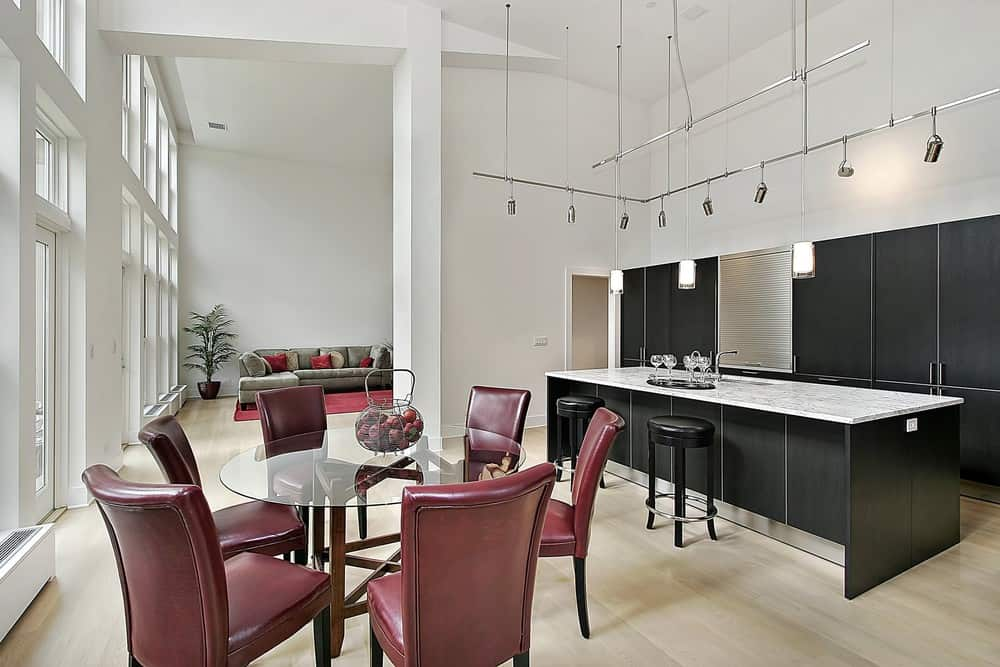 Kitchen space with very high ceilings towering up with bright white walls. In the center of the open concept, space sits a modern kitchen with black cabinets and black island base. The long island has a sleek white countertop.