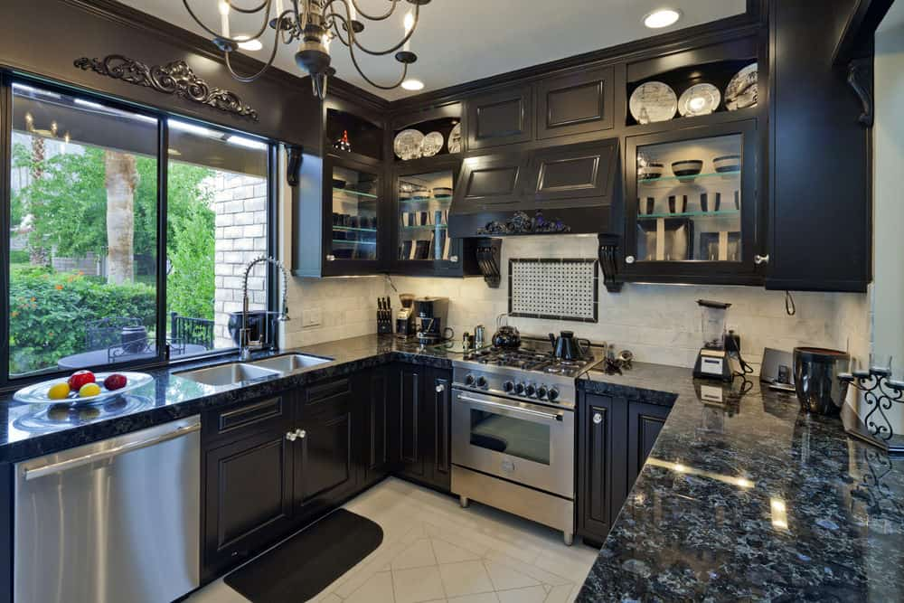 Busy kitchen with a country style that has black cabinets and dark gray granite countertops. The black is somewhat offset with stainless steel appliances, white floor, off-white backsplash and large window.