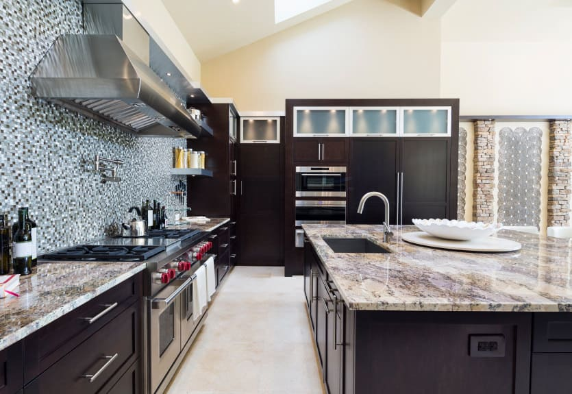 New kitchen with black cabinets throughout with light beige and dark brown granite. A massive blue, dark gray and white tile backsplash I think makes this kitchen too busy given the granite countertops. The beautiful, simple black cabinets get lost amidst the busyness of the backsplash and countertops.