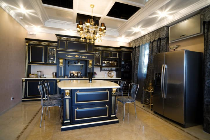 Elegant kitchen features black cabinetry and breakfast island with gold lining illuminated by a luxurious chandelier that hung from the coffered tray ceiling.