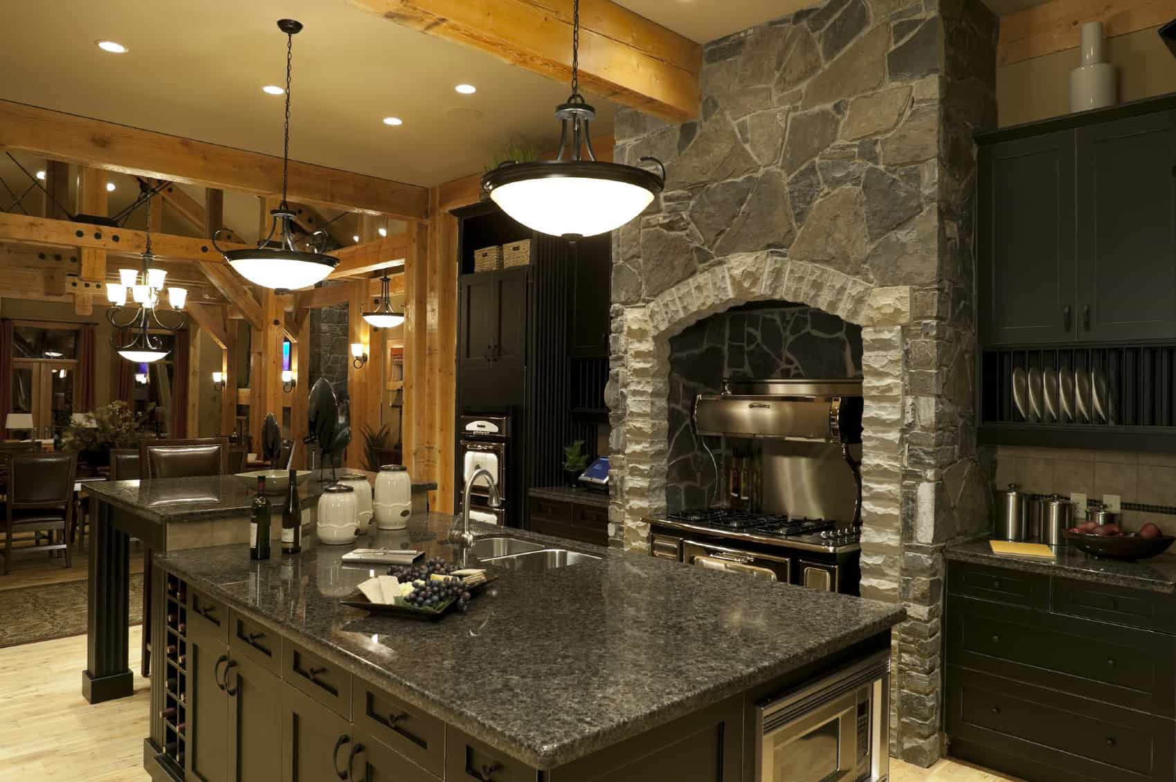 Stunning luxury kitchen with black cabinets, countertops all around a gray flagstone fireplace. The wood floor is made up of very light wood and there are light wood beams supporting the ceiling. The extensive wood contrasts very nicely with the black cabinets.