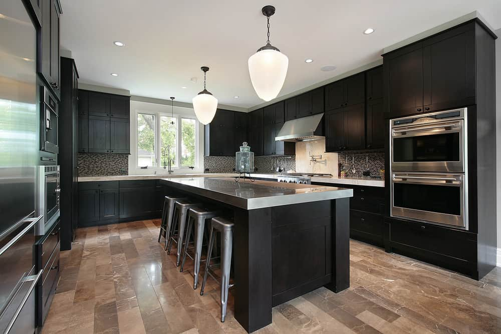 A pair of lovely pendant lights illuminate this kitchen boasting black cabinetry and breakfast island with gray countertop and bar stools.