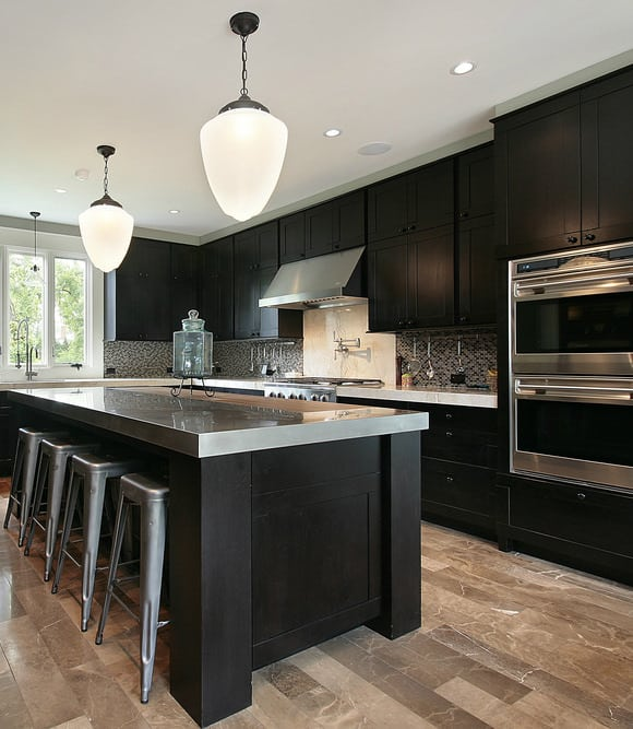 Contemporary black kitchen with black and white backsplash and stainless steel countertops and appliances.