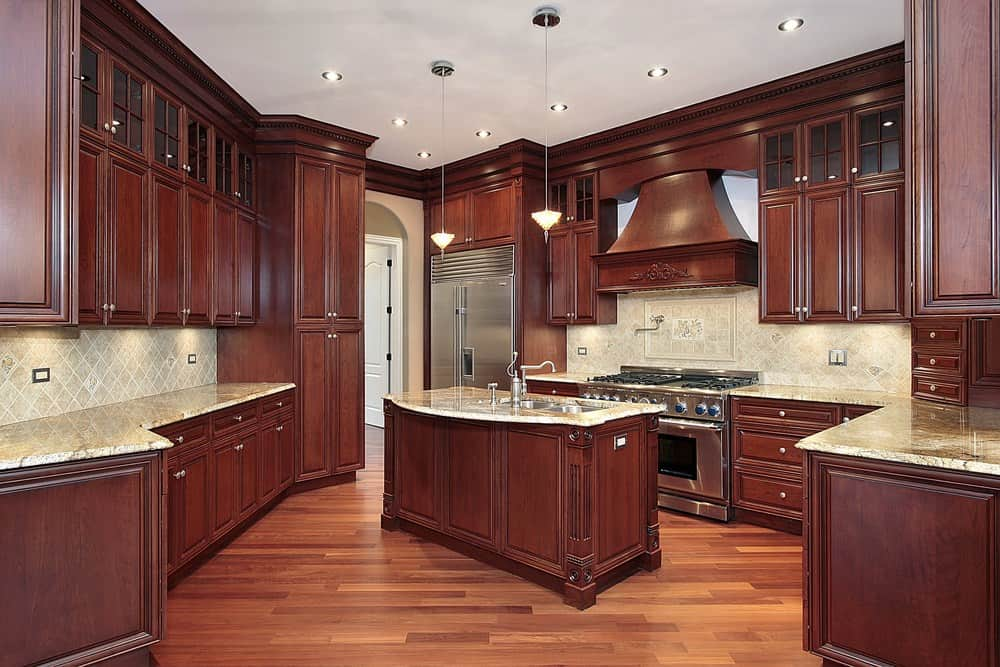 Another deep red-brown cabinet kitchen with matching island offset with light beige backsplash and granite countertops. Check out that matching ornate wood range hood.