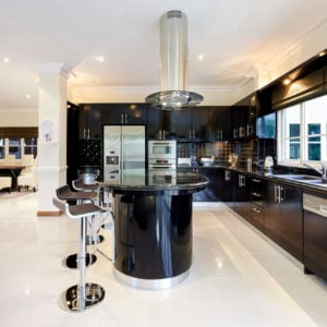 Large l-shaped kitchen with black cabinets and a black island
