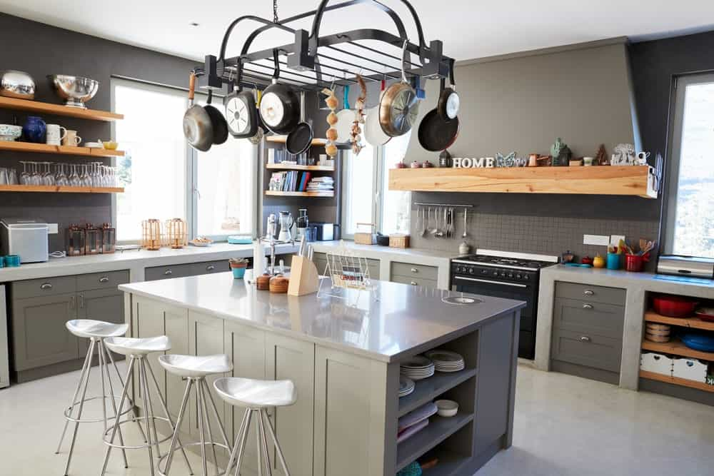 Gray kitchen with pot rack, ledges, open shelving, and an eat-in-kitchen island.