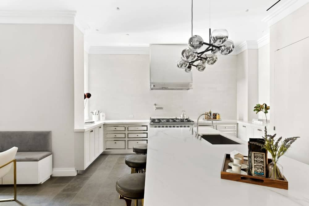 A contemporary kitchen with a minimalist design showcasing an absence of custom cabinets. The area offers a large center island with a breakfast bar and an undermount sink paired with chrome fixtures.