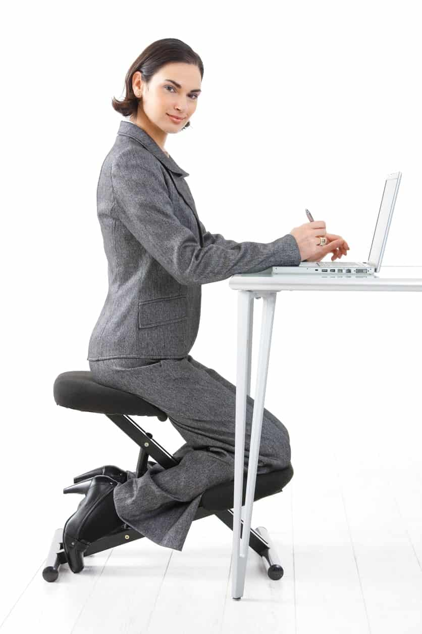A woman poses and sits on a kneeling chair while working on her laptop on her workstation.
