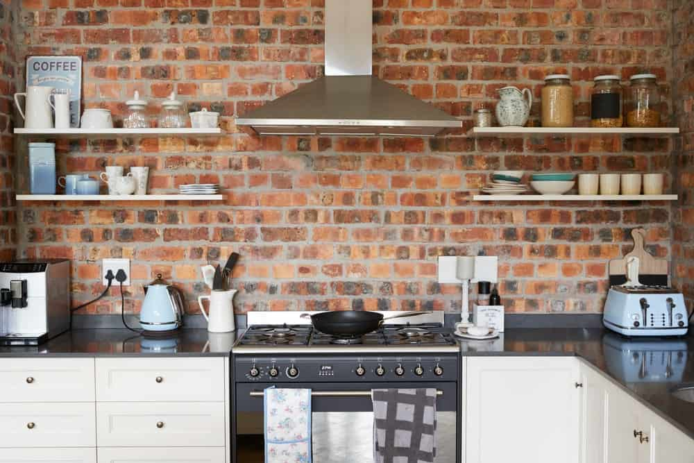 Urban chic kitchen with exposed brick wall, floating shelves, and stainless steel appliances.