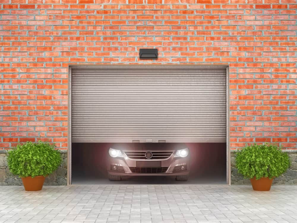 Car coming out from a lifting garage door.